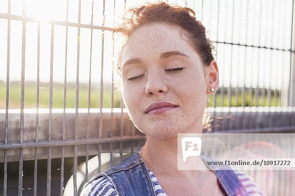Junge Frau mit geschlossenen Augen am Zaun