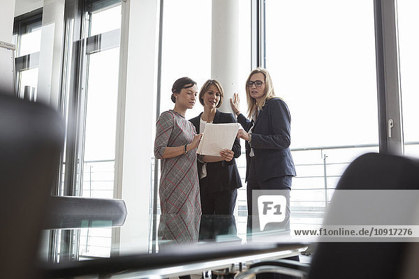 Three businesswomen discussing documents at the window