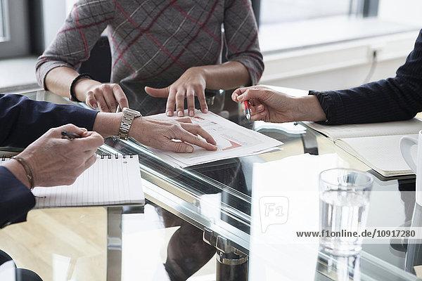 Drei Geschäftsfrauen diskutieren in einer Sitzung über ein Dokument