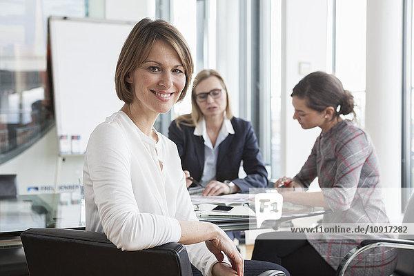 Porträt einer lächelnden Geschäftsfrau in einer Besprechung