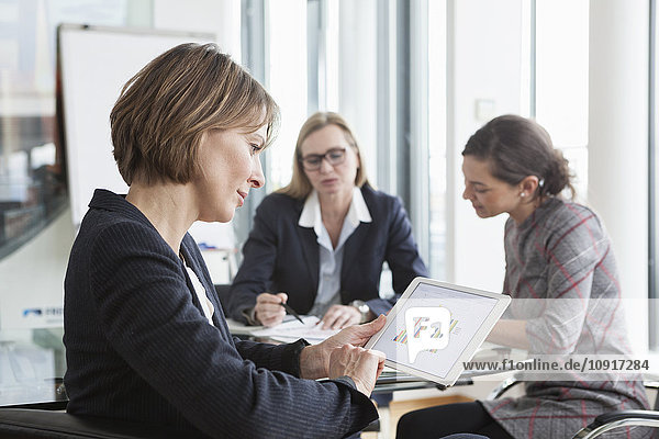 Businesswoman using digital tablet in a meeting
