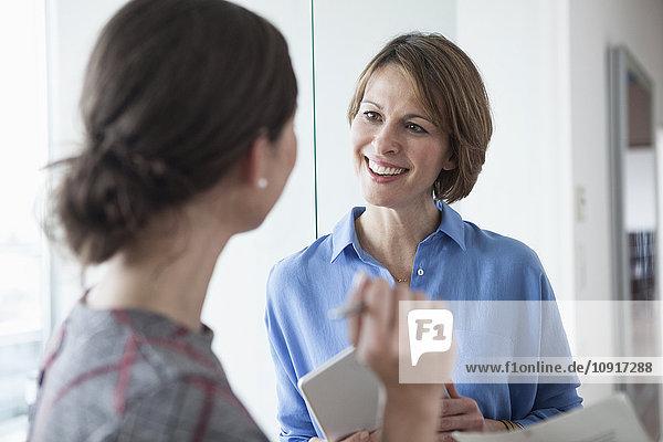 Zwei Geschäftsfrauen im Büro im Gespräch