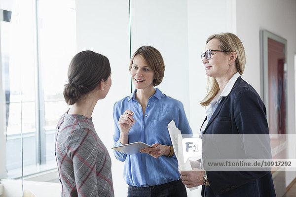 Drei Geschäftsfrauen diskutieren im Amt