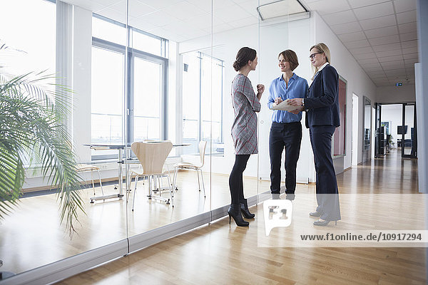 Drei Geschäftsfrauen diskutieren über die Bürohalle