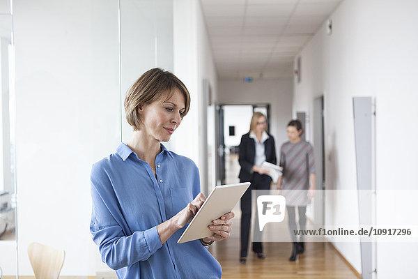 Geschäftsfrau mit digitalem Tablett im Bürogeschoss
