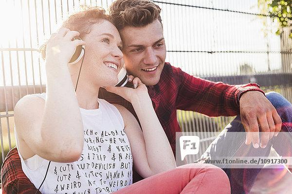 Lächelndes junges Paar am Zaun mit Kopfhörer