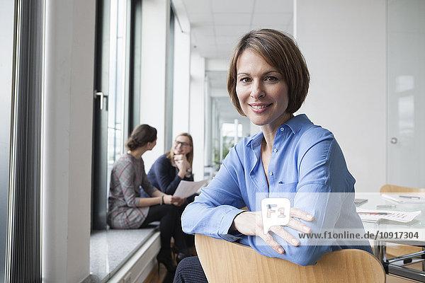 Porträt einer lächelnden Geschäftsfrau mit Kollegen im Hintergrund