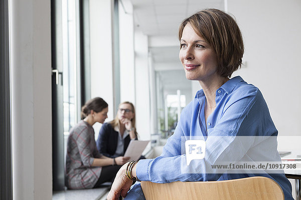 Lächelnde Geschäftsfrau mit Kollegen im Hintergrund