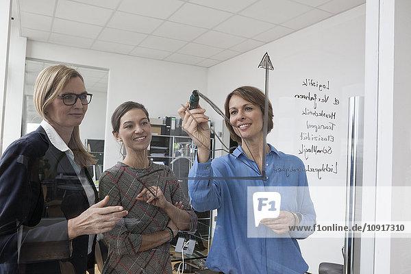Geschäftsfrau mit zwei Kollegen beim Zeichnen von Diagrammen auf Glasscheibe im Büro