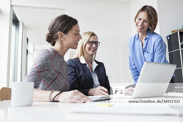 Drei glückliche Geschäftsfrauen teilen sich den Laptop im Büro