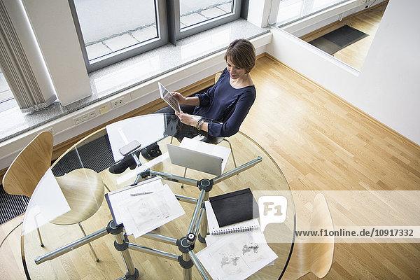 Geschäftsfrau mit digitalem Tablett und Laptop am Bürotisch