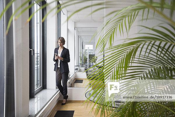 Geschäftsfrau beim Blick auf das Handy am Bürofenster