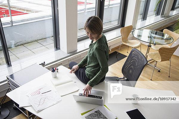 Geschäftsfrau mit Laptop am Schreibtisch
