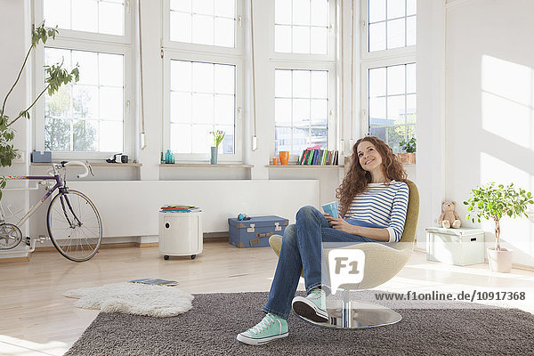Entspannte Frau zu Hause im Sessel sitzend