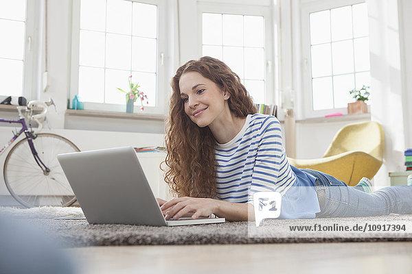 Frau zu Hause auf dem Boden liegend mit Laptop