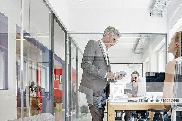 Manager im Gespräch mit Kollegen im Büro