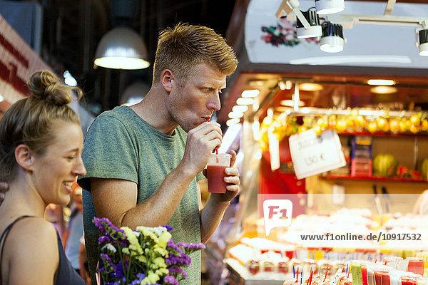 Mann trinkt Smoothie auf einem Straßenmarkt