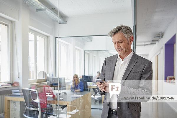 Reife Geschäftsleute im Büro mit Smartphone