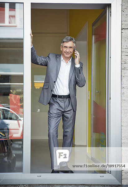 Geschäftsmann  der in der Tür seines Büros steht und ein Mobiltelefon hält.