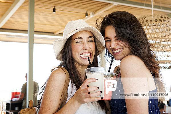 Zwei junge Frauen trinken Cocktails in der Strandbar