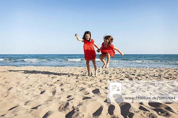 Zwei kleine Schwestern springen zusammen am Strand.