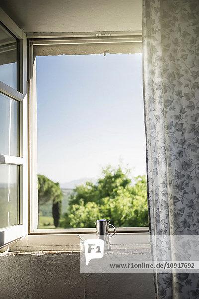 Espressodose und Kaffeetasse am Fenster