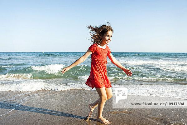 Glückliche kleine Schwestern  die am Strand spazieren gehen.