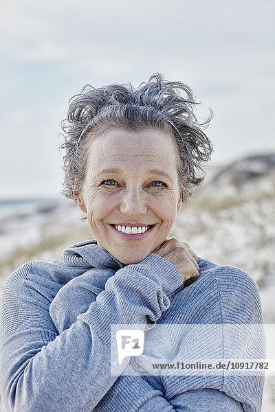 Porträt einer lächelnden Frau am Strand