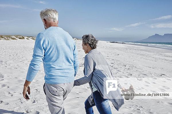 Rückansicht des Paares beim Spaziergang am Strand