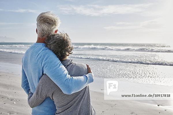 Rückansicht des Paares am Strand mit Blick auf das Meer