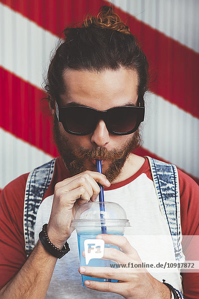 Porträt eines jungen Mannes mit Sonnenbrille  der Erfrischungsgetränk trinkt.