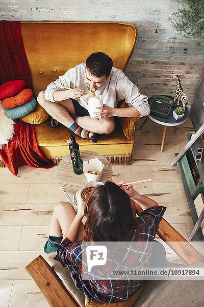 Junges Paar isst chinesisches Essen zum Mitnehmen zu Hause