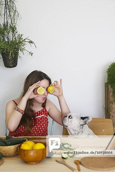 Französische Bulldogge beobachtet Frau  die ihre Augen mit Zitronenhälften bedeckt. Französische Bulldogge beobachtet Frau, die ihre Augen mit Zitronenhälften bedeckt.