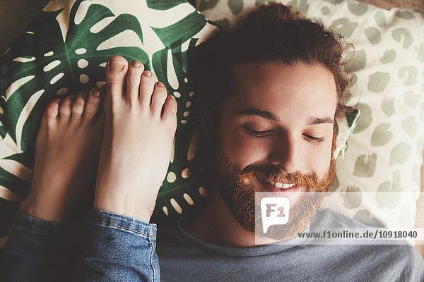 Portrait eines lächelnden jungen Mannes  der neben den Füßen seiner Freundin liegt.