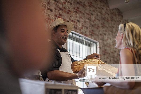 Ladenbesitzer im Geschäft hilft dem Kunden  Weißbrot