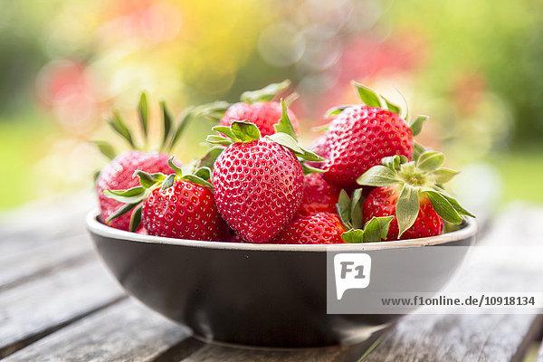 Schale mit Erdbeeren auf Gartentisch aus Holz