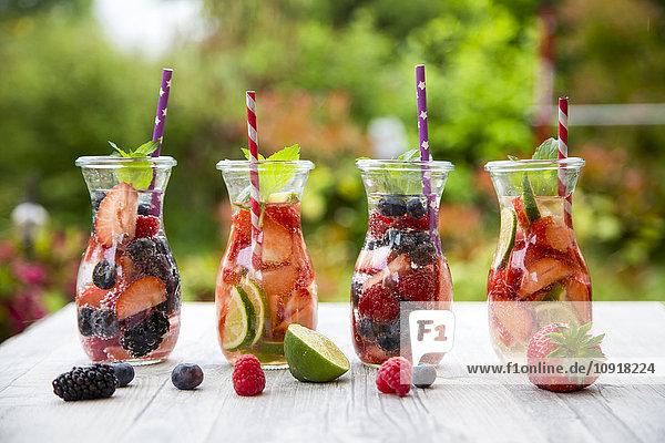 Vier Glasflaschen entgiftendes Wasser mit verschiedenen Früchten