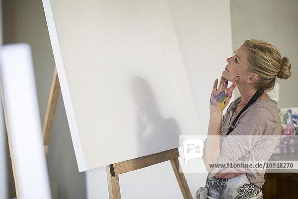 Frau beobachtet die Leinwand  bevor sie das Kunstwerk im Heimstudio aufbaut.