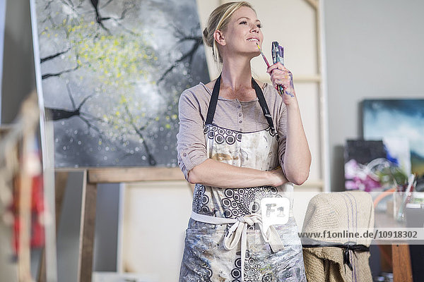 Female painter with paintbrushes in her hand