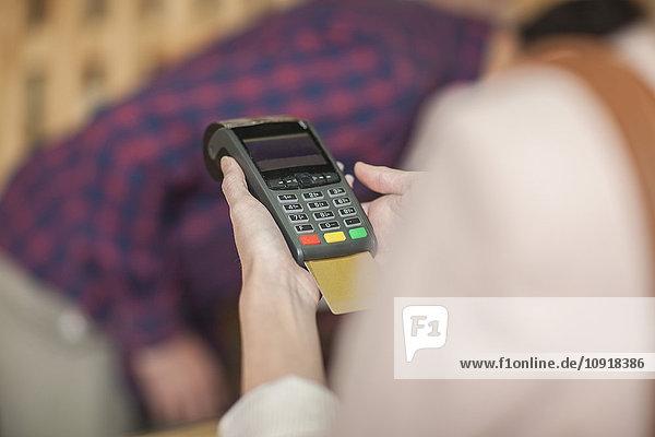 Frau im Geschäft mit Kreditkarte bezahlen