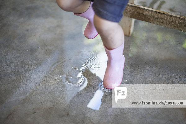 Kleines Mädchen mit rosa Gummistiefeln in Pfütze springend Kleines Mädchen mit rosa Gummistiefeln in Pfütze springend