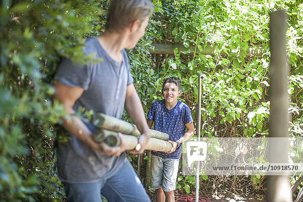 Father and son carrying wooden poles in garden
