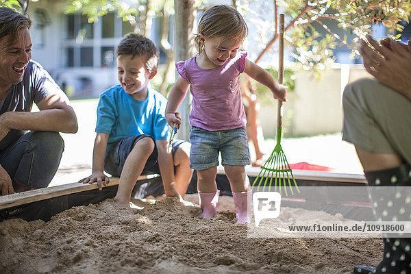 Mädchen mit Familie beim Spielen im Sandkasten