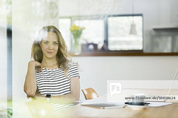 Porträt einer selbstbewussten Frau mit Laptop am Tisch