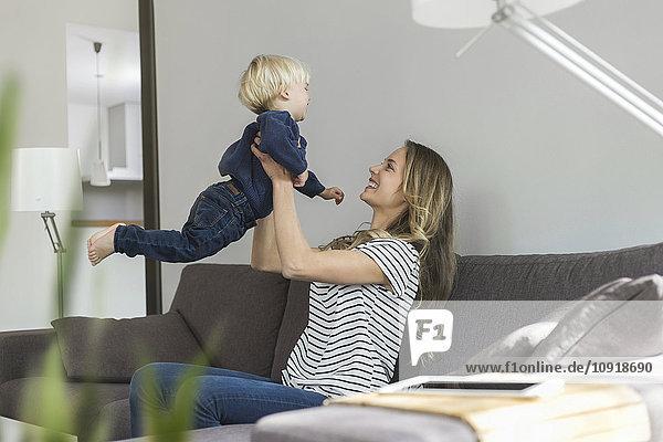 Mutter und Sohn zu Hause spielen auf der Couch