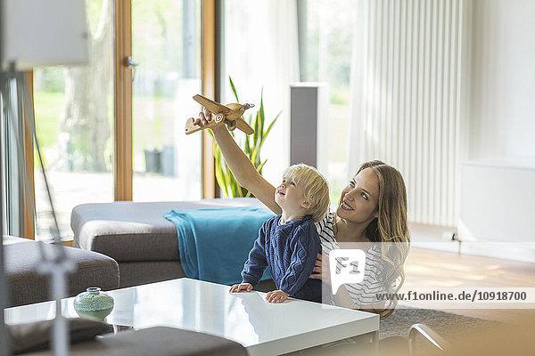 Mutter und Sohn beim Spielen mit dem Spielzeugflugzeug im Wohnzimmer