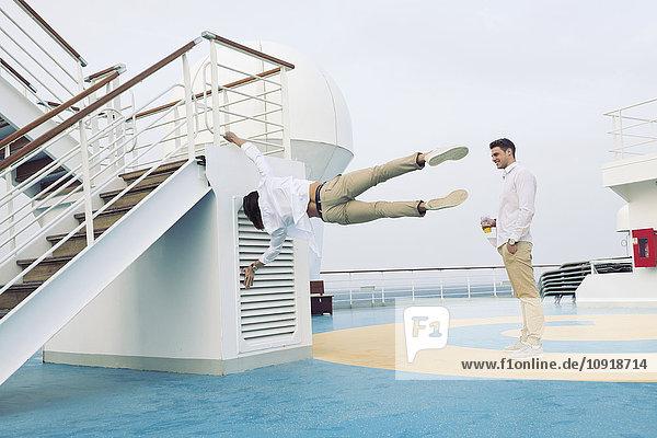 Zwei junge Männer  die auf einem Kreuzfahrtschiff herumspielen und Gymnastik machen.