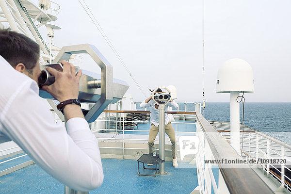 Zwei junge Männer auf einem Schiff  die sich durch Teleskope beobachten.