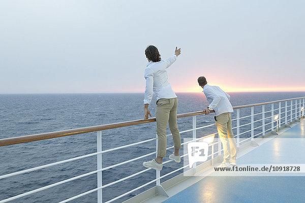 Junge Männer  die an Deck des Schiffes stehen und den Sonnenuntergang beobachten.