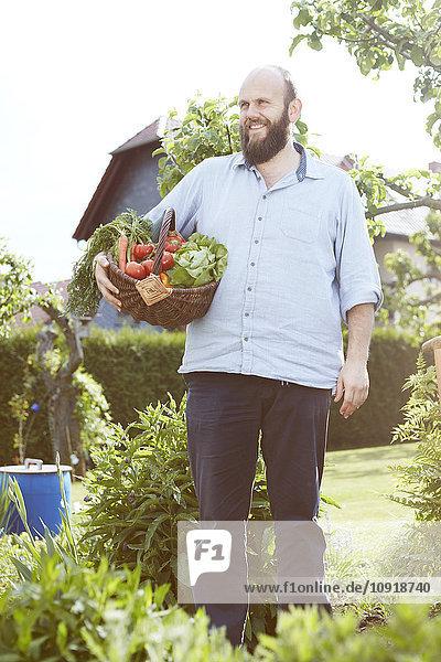 Junger Mann im Garten stehend  Korb mit frischem Gemüse